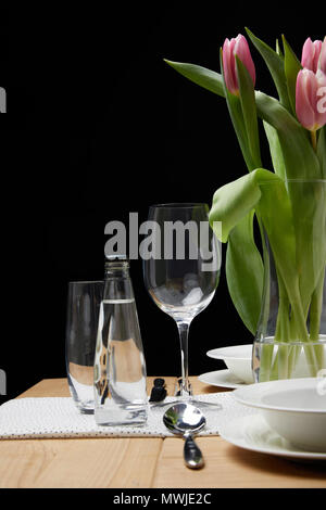 Vase with flower bouquet on table with festive tableware - Stock Photo
