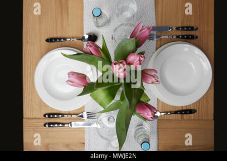 Dinnerware with plates on table with flowers in vase - Stock Photo