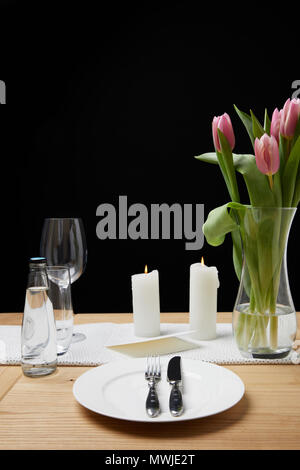 Vase with flower bouquet and candles on table with festive tableware - Stock Photo