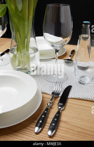 Dinnerware with glasses on table next to bouquet in vase - Stock Photo