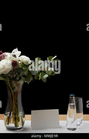 Tender Flowers In Vase With Water Bottle And Empty Glasses On Table