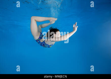 Girl curled into a wheel under water in the pool. Underwater acrobatics - Stock Photo