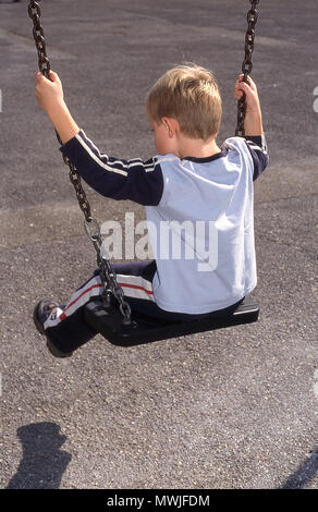 Six year old boy on a swing (rear view) - Stock Photo