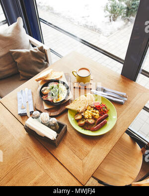 Brunch in restaurant with fried eggs served and coffee - Stock Photo