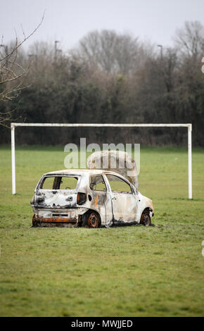 Burned Out stolen car abandoned on a community football pitch next to a council estate in Hampshire - Stock Photo