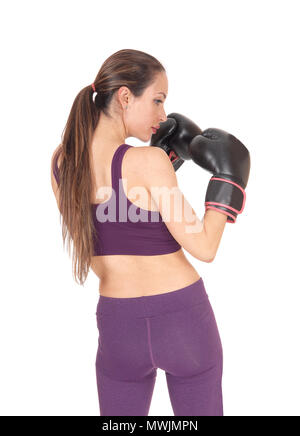 A young slim woman in exercising outfit standing from the back, holding up her boxing cloves, isolated for white background - Stock Photo
