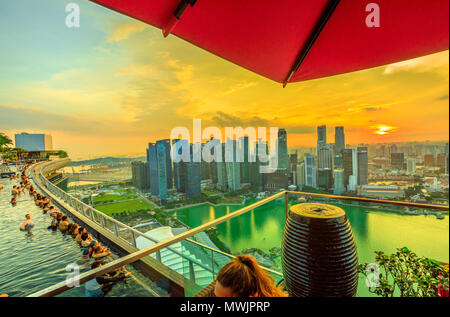 Singapore - May 3, 2018: CE LA VI Club Lounge's Sky Deck Area overlooking Infinity Pool of Skypark that tops the Marina Bay Sands Hotel. Financial district skyline on background. Sunset shot. - Stock Photo