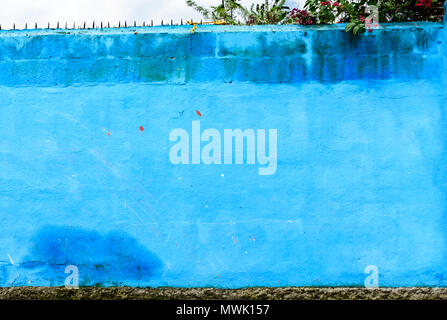 Blue painted exterior property wall with nails in top for security in Guatemala, Central America - Stock Photo
