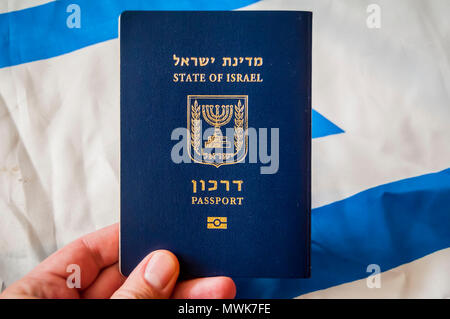 Hand holding the passport of the State of Israel, Israeli flag on the background. Israel citizenship concept, Israeli 'darkon' passport illustrative - Stock Photo