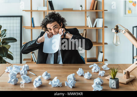 portrait of stressed businessman biting blank paper while while sitting at workplace in office - Stock Photo