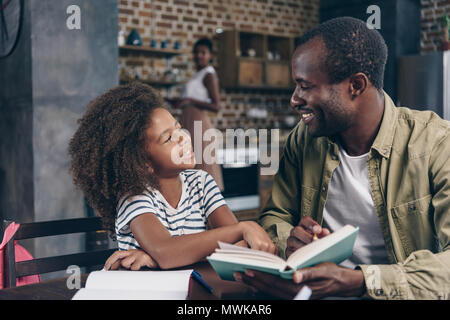 Father and daughter reading a book together at the kitchen table - Stock Photo