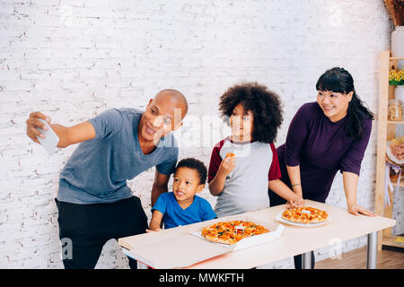 Happy parents and little boy and girl having a meal and taking selfie by smartphone at home. Family and parenthood concept - Stock Photo
