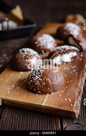 Delicious cocoa biscuits with coconut filling, decorated with chocolate and grated coconut - Stock Photo