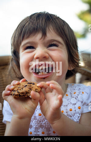 A 16-month-old girl bursting out laughing when she eats a cookie. - Stock Photo