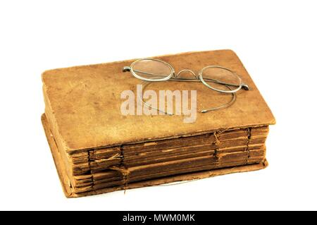 Very old and worn book with antique round eyeglasses. Isolated on white background. - Stock Photo