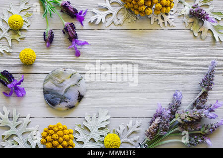 Dendridic Agate Palm Stone with Lavender and Yellow Flowers on White Table - Stock Photo