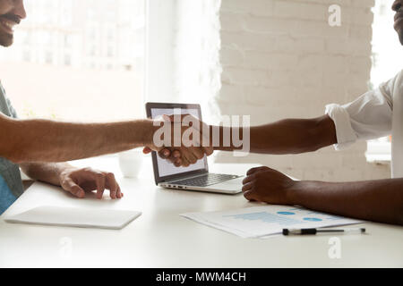 Close up of business partners shaking hands after making agreeme - Stock Photo