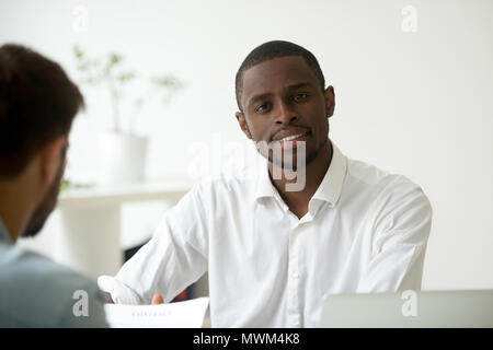 Smiling African American worker looking at camera in office - Stock Photo