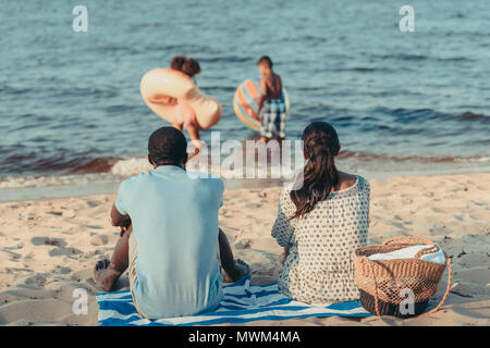 back view of african american parents looking at kids playing in sea - Stock Photo