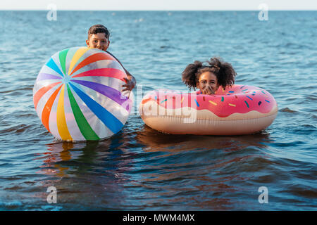cute smiling african american brother and sister having fun with beach ball and swimming tube in sea - Stock Photo