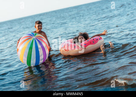 happy african american siblings having fun with beach ball and swimming tube in sea - Stock Photo