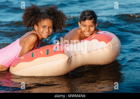 happy african american brother and sister having fun together on swimming tube - Stock Photo