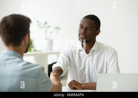 Glad African American employer handshaking hired Caucasian job a - Stock Photo