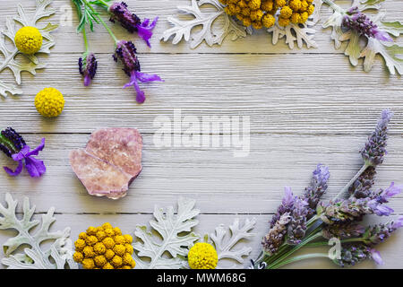Lepidolite with Lavender and Yellow Flowers on White Table - Stock Photo