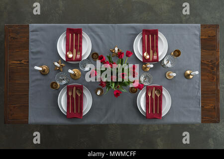top view of rustic table setting with red tulips bouquet, tarnished cutlery, wine glasses, candles and empty plates on tabletop - Stock Photo