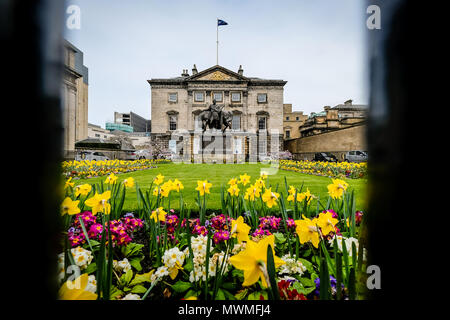 Edinburgh, Scotland - April 27, 2017: Royal bank of scotland seen through the fence, with flower garden in the foreground on a cloudy day. - Stock Photo