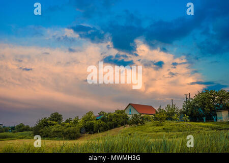 village house with a red roof stands in a green field under a beautiful sunset sky with clouds of different colors - Stock Photo
