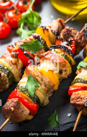 Grilled shish kebab or shashlik with vegetables  on black stone table. Pork meat. Barbeque meat dish. - Stock Photo