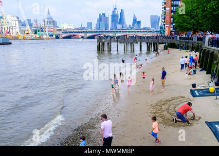 People enjoying the sandy beach of River Thames foreshore at low tide. - Stock Photo