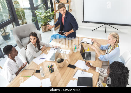 multicultural business team discussing new strategy and ideas at meeting in office - Stock Photo