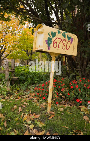 Close-up of a hand painted and decorated mailbox on a post on a residential front lawn in autumn - Stock Photo