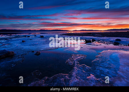 Sunrise over frozen ice on the shores of Lake Tahoe in winter. - Stock Photo