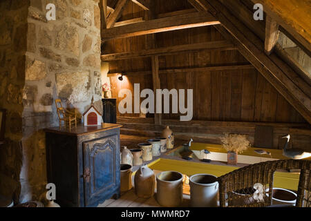 Small blue wooden armoire with ceramic pots and jugs on the upstairs floor inside an old (1752) French regime cottage style residential home - Stock Photo
