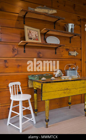 Small white high-chair and old yellow antique table with collectibles in sunroom inside a cottage style flat log profile and timber home - Stock Photo