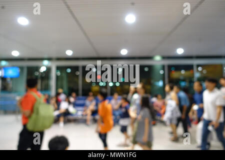 Blurred defocused image of passengers check in at the check-in counter at the international airport. Blurry background of people waiting in line. - Stock Photo