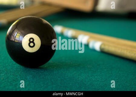 Eight black ball on a green table with cue sticks - Stock Photo