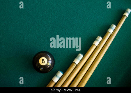 Eight black billiard ball on a green billiard table next to a group of a cue sticks - Stock Photo