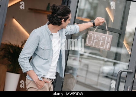 young boutique owner hanging open sign on the door of his shop - Stock Photo