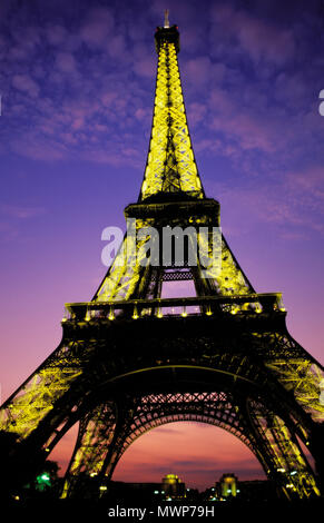 Eiffel Tower, close view on Champ de Mars looking up at dusk, depicting lights on a with little fluffy clouds and twilight glow, Paris, France - Stock Photo