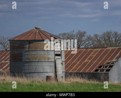 Rusty metal grain bin with number 40 on the door in front of an abandoned barn in rural America - Stock Photo