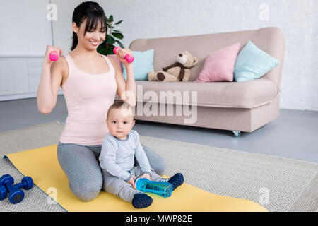 young smiling mother working out on yoga mat with her little child at home - Stock Photo