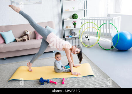 young mother practicing yoga in One Legged Downward-Facing Dog pose while her little child sitting on mat at home - Stock Photo