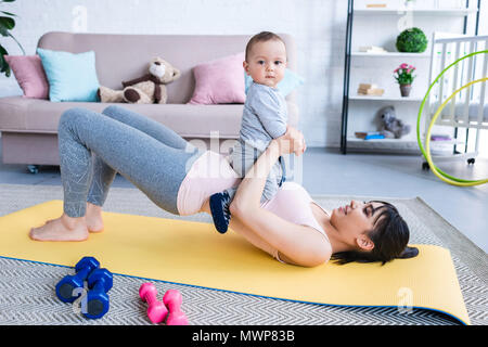 young happy mother working out on yoga mat with her little child at home - Stock Photo