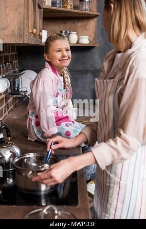 side view of smiling preteen girl sitting on counter and watching mother cooking at home - Stock Photo