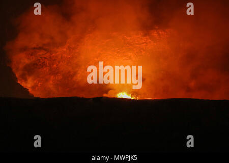Bright orange and red hues of flowing lava at Hawaii Volcanoes National Park - Stock Photo