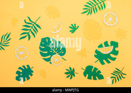 Tropical leaves pattern. Green monstera and fern leaves with orange and lemon slices on a bright yellow background. Summer vacation concept with paper craft fruits - Stock Photo